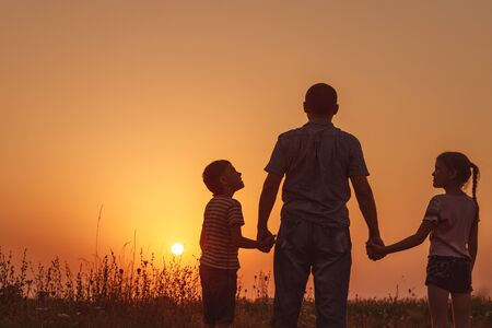 Father and children standing in the park at the sunset time. People having fun on the field. Concept of friendly family and of summer vacation. Stockfoto