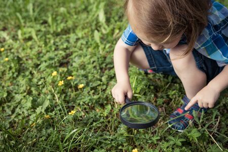 Happy little boy exploring nature with magnifying glass at the day time. Concept of interesting lesson.