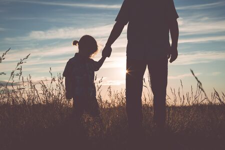 Father and sad son standing in the park at the sunset time. People are sad in the field. Concept of friendly family.