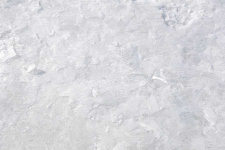 water frozen: Closeup view on beautiful textured winter seaon background of cold frozen water in shiny white ice with snow and no people