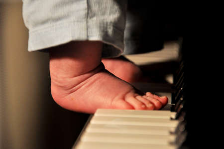 babyboy: Closeup view on male babyboy bare feet with small toys playing on piano forte key board musical instrument with warm light indoor, horizontal picture