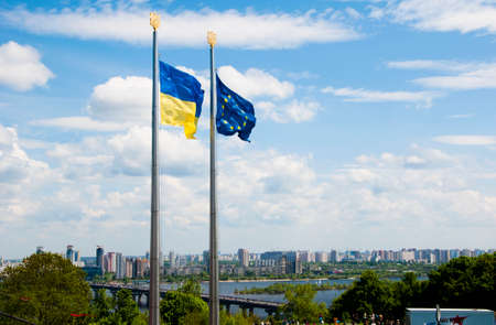 dniper: Beautiful sunny spring or summer landscape with two national flags of Ukraine and European Union yellow and blue colors in wind on cloudy sky background, horizontal picture