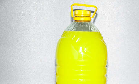 economical: Closeup of one economical closed large plastic bottle of bright yellow color soft soap or paint indoor Stock Photo