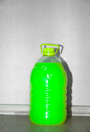 economical: Closeup of one economical closed large plastic bottle of bright green color soft soap or paint indoor Stock Photo