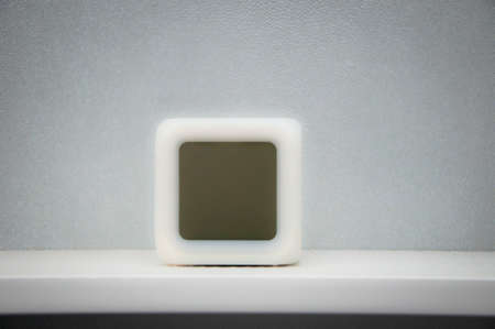 white cube: Conceptual blurred closeup of square shape empty white cube clock standing on office shelf on grey wall background, copy space Stock Photo