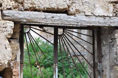 Ventana vieja abandonada con la barra de hierro en la construcción de piedra con planta verde que crece en el interior
