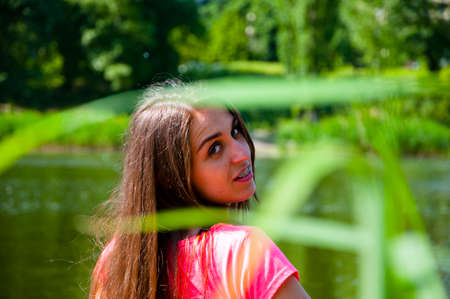 cute braces: young sexy smiling woman or girl with pretty cute face and long brunette hair in pink shirt has braces or brackets on teeth near river or sea water sunny outdoor on natural background