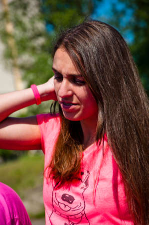cute braces: young sexy smiling woman or girl with pretty cute face and long brunette hair in pink shirt has braces or brackets on teeth sunny outdoor on natural background