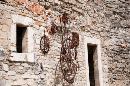 stony: old iron metallic clock on stony wall of historic building house sunny outdoor Stock Photo