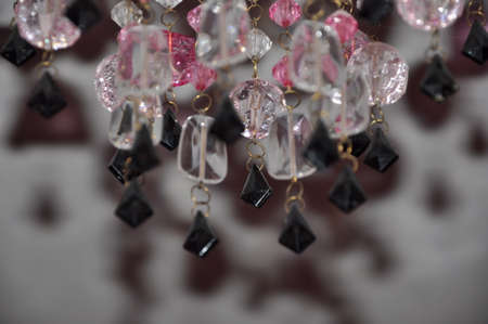 beautiful crystal or gemstones from plastic or glass white pink and black color on chain of chandelier lamp or lustre on blurred or defocused background, closeup Stock Photo