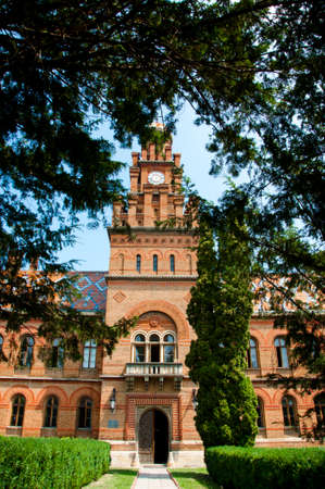 campus tour: beautiful historical building of Chernivtsi national university religious seminary of red brick facade with green trees and bushes sunny outdoor in Ukraine