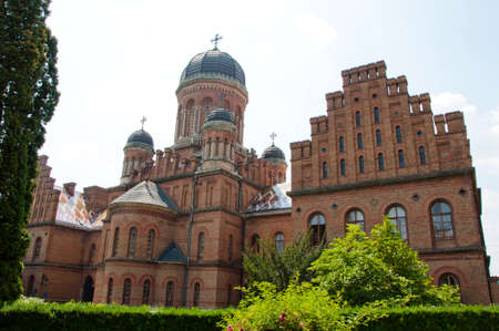 beautiful historical building of Chernivtsi national university religious seminary of red brick facade with green trees and bushes sunny outdoor in Ukraine