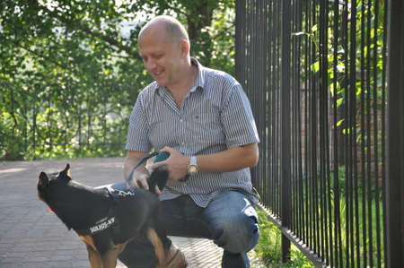 handsome bald man with smiling face near iron fence with beautiful cute black and brown dog pet friend outdoor in summer on green sunny day Stock Photo