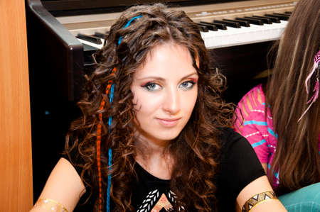 face cloth: young cute sexy woman or girl with pocahontas ethnic tribal fashionable makeup on pretty face has feather in curly stylish brunette long hair in indie cloth and golden tattoo at piano, portrait Stock Photo