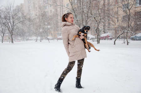 christmas military: pretty cute young smiling girl or sexy woman in beige winter coat and camouflage military jeans snowy cold winter on natural white background stands in snow and snowflakes with black dog or puppy pet