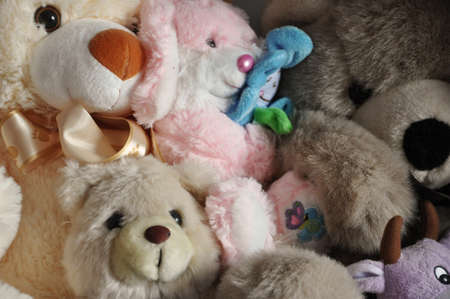 childlike: many fluffy cute stuffed soft plush toys animal of bear, rabbit, cow and hare as childish or childlike background Stock Photo