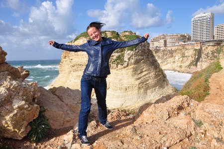 Pigeon Rocks in Raouche, Lebanon. happy girl at mediterranean sea and beautiful mountains in water. woman tourist in lebanon, beairut. wanderlust and traveling to middle east. Raouche rocks and girl Stock Photo - 103260822