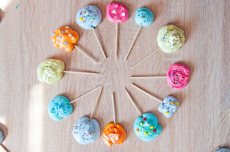 copy space meringue round shape frame. punchy pastels concept. mock up meringues on wooden background. vintage photo with sweets on sticks. flat lay dessert background frame for copy space. Stock Photo