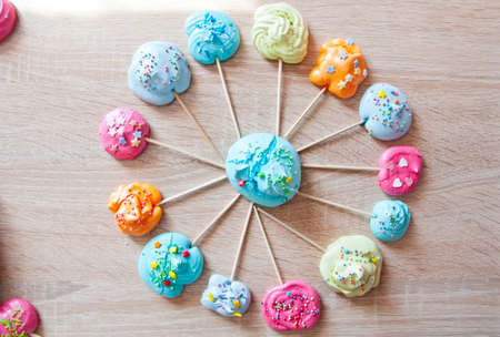 candy shop icon. meringue on stick as colorful sweets with sprinkles. meringue in roung shape on wooden background. fair and circus mood. bubble gum on wooden stick. mock up vintage dessert. Stock Photo
