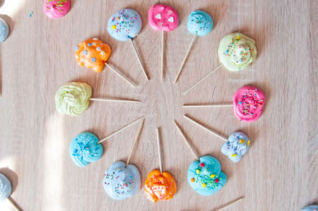 pinwheel or windmill shape meringues. childhood and happiness concept. candy shop and confectionary. circle of meringue sweets on wooden table. mock up dessert background.