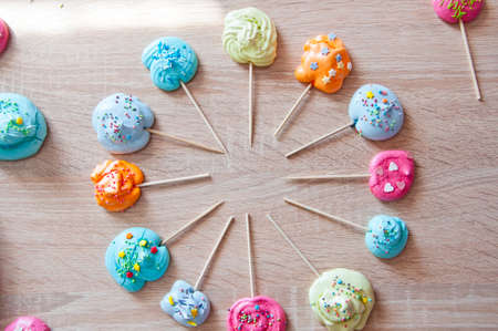 color splash. summer time in amusement park. meringue on candy stick in round shape as emblem for confectionary or cafe. cooking meringues with colorful sprinkles. top view dessert background.
