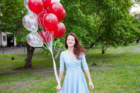 Crazy party girl. happy woman with party birthday baloons outdoor in summer.