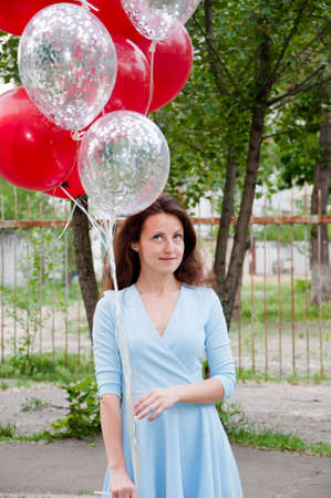 Feeling playful. playful young woman holding red balloon bouquet and smiling while standing against outdoor background