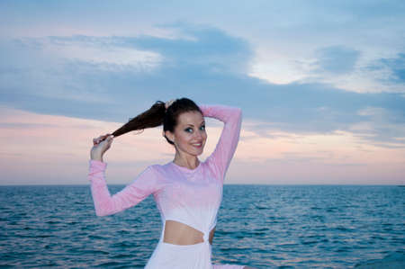 Young woman in summer dress looking to a sea in sunset Stock Photo - 103285886