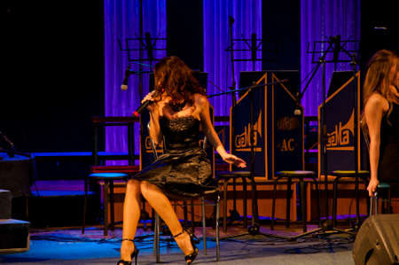 jazz singer. sexy woman in black cocktail dress singing while sitting on chair at stage with mic. elegance and look. fashion and beauty style. sensual girl singer like music. karaoke and vocal school