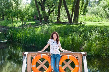 lifebuoy at river port with sexy young woman in summer vacation travel Stock Photo