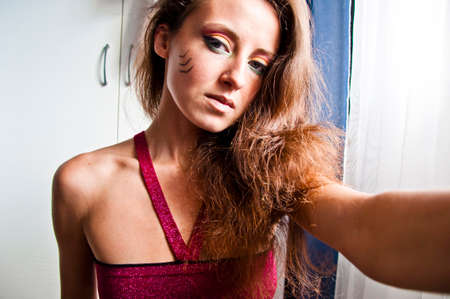 young cute sexy woman or girl with pocahontas ethnic tribal fashionable makeup on pretty face with long brunette hair making selfie photo, portrait