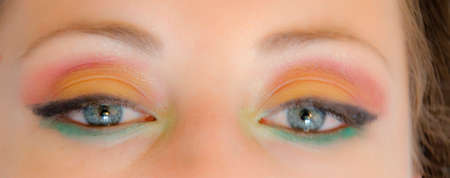 female eyes of young cute sexy woman or girl with pocahontas ethnic tribal fashionable bright colorful makeup on pretty face as blurred or defocused background, closeup