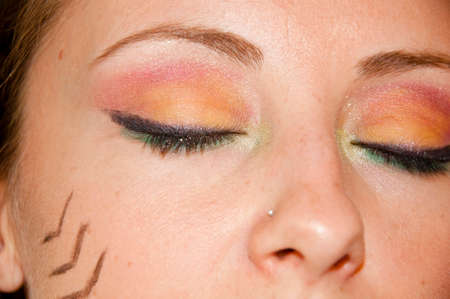 young cute sexy woman or girl with pocahontas ethnic tribal fashionable bright colorful makeup on pretty face, closeup