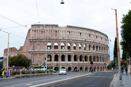 Rome, Italy - May 01, 2018: Colosseum architecture in Rome with tourists. Destination place - Colosseum. Traveling and vacation in Europe, European Union. Colosseum is a historical building Stock Photo - 104180990
