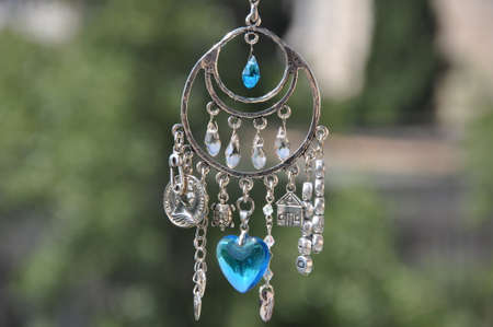 Magical and miraculous. Luck amulet hung out outdoor. Silver amulet with gems and pendants. Believing in magic protecting the holder of amulet. Jewelry charm or talisman. Name amulet for good luck.