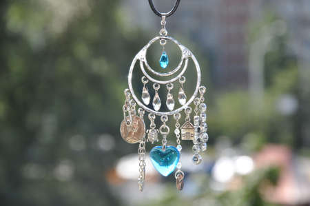 May the luck be with you. Luck amulet hung out outdoor. Name amulet for good luck. Silver amulet with gems and pendants. Believing in magic protecting the holder of amulet. Jewelry charm or talisman. Stock Photo