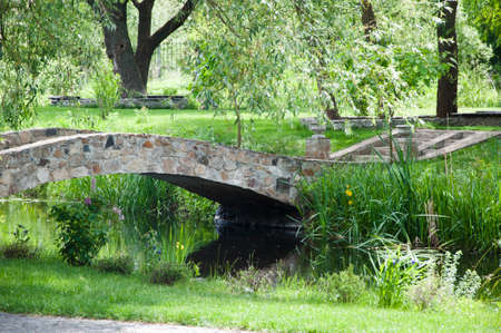 Environmentally sustainable design. Landscape architecture and landscaping. Landscape park. Stone bridge on summer landscape. Old stone bridge in botanical garden. Summer vacation and wanderlust.
