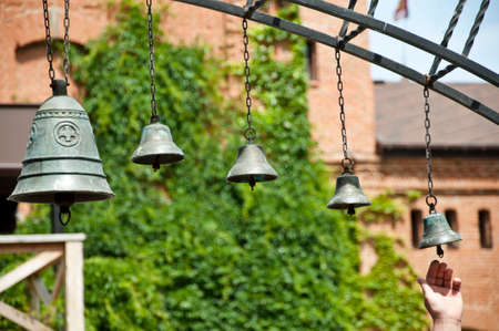 Calling to prayer. Church bells hanging outdoor. Metal bells on metallic chains hung on arc in church yard. Bells ringing on wind. Calling to christian mass or service of worship. Stock Photo