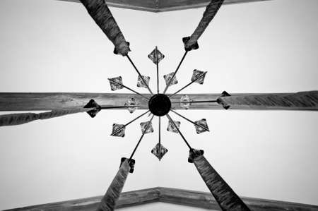 Master in ceiling. Decorative lamp hanging from ceiling. Old ceiling. Wood beam ceiling. Classic overhead interior surface. Vintage or retro interior design. Architectural structure, black and white.