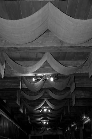 Ceiling height. Wood beam ceiling with draped textile. Ceiling drapery. Decorative old ceiling with drapes. Vintage or retro interior room design. Classic overhead interior surface, black and white. Stock Photo