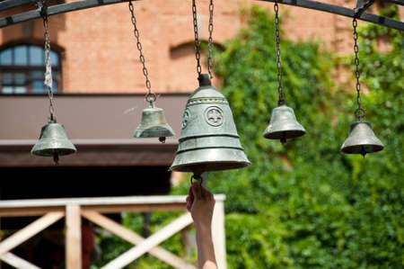 Believed to drive out demons. Calling to christian mass or service of worship. Church bells hanging outdoor. Metal bells on metallic chains hung on arc in church yard. Bells ringing on wind.