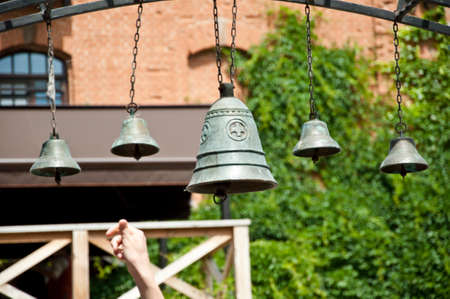 The art of ringing a set of tuned bells. Church bells hanging outdoor. Bells ringing on wind. Metal bells on metallic chains hung on arc in church yard. Calling to christian mass or worship service.