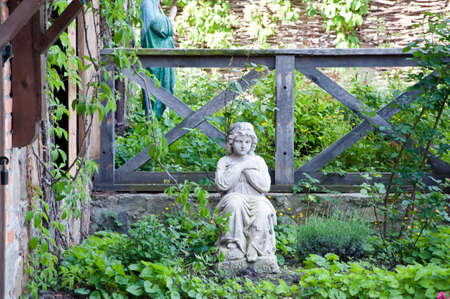 Tranquillity and peace. Statue of human in summer garden. Carved stone human figure. Garden or park decor. Sculpture in stone outdoor. Stone statue. Statuary artwork. Sculptural arts.