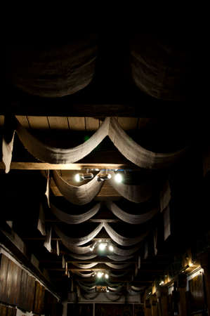Simle but pompous. Ceiling drapery. Decorative old ceiling with drapes. Vintage or retro interior room design. Wood beam ceiling with draped textile. Classic overhead interior surface. Stock Photo
