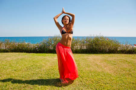 Suntan. Woman dancing with sexy body. Summer vacation and travel. Sexy woman with fit belly. Spa and relax. Perfect body of belly dancer. Sensual girl on sea beach. Eastern beauty. Cool and sexy.