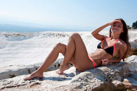Sexy woman with fit suntan body. Natural travertine pool terrace in Pamukkale. Cotton castle in southwestern Turkey. Summer vacation in Pamukkale. Dead sea salty shore. Sexy girl. Soapy pleasure. Stock Photo