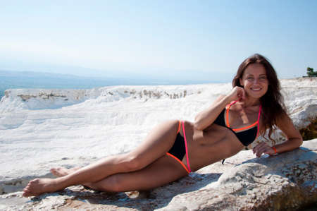 Time to relax. Dead sea salty shore. Sexy girl. Cotton castle in southwestern Turkey. Summer vacation in Pamukkale. Natural travertine pool terrace in Pamukkale. Sexy woman with fit suntan body.