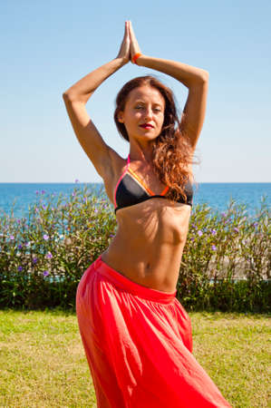Sensual girl on sea beach. Eastern beauty. Perfect body of belly dancer. Summer vacation and travel. Suntan. Woman dancing with sexy body. Sexy woman with fit belly. Spa relax. Young and beautiful.
