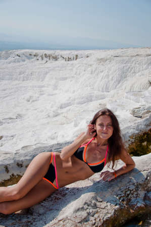 Dead sea salty shore. Sexy girl. Cotton castle in southwestern Turkey. Natural travertine pool terrace in Pamukkale. Sexy woman with fit suntan body. Summer vacation in Pamukkale. Woman at spa. Stock Photo