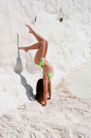 Summer vacation in Pamukkale. Cotton castle in Turkey. Sport. Dead sea salty shore. Sexy girl gymnast. Natural travertine in Pamukkale. Beach yoga. Sexy woman with fit suntan body. Working out. Stock Photo